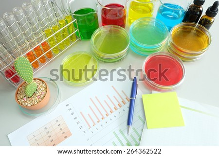 work table in laboratory and colorful fluid in glassware - stock photo