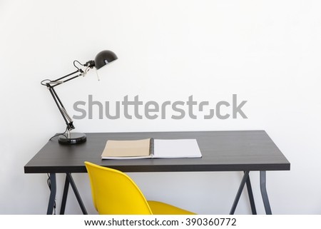 work table with book lamp and yellow chair at home - stock photo