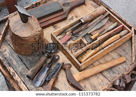 work table with old tools of the artisan shoemaker - stock photo