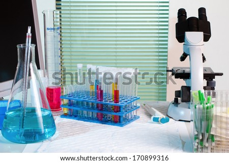 Workbench with glass material scientist, tubes, microscope and screen in chemical lab