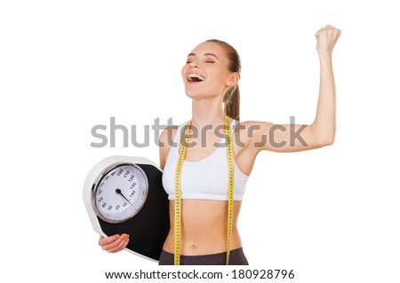 Worked off her excess weight. Happy young woman in sports clothing holding weight scale and gesturing while standing isolated on white - stock photo