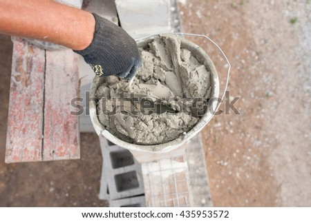worker aligns with a spatula, lay brick cinder blocks. - stock photo
