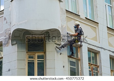 worker alpinist in a protective mask working with sander for smoothing wall surface of the building