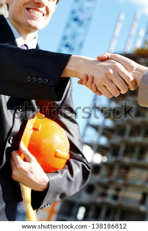 Worker and architect shaking hands at construction site - stock photo