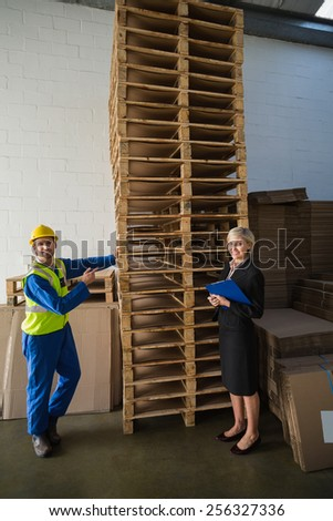 Worker and his manager in front of a stack of pallet in a large warehouse - stock photo