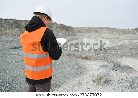 Worker and quarry in background - stock photo