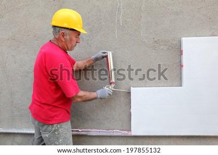 Worker applying polyurethane expanding foam glue with gun applicator - stock photo