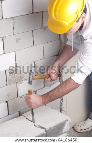 worker at building lot with helmet and hammer - stock photo