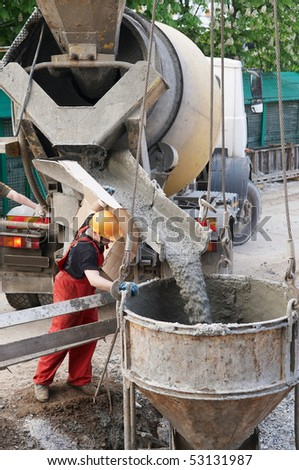 worker builder controlling concrete filling process at construction site - stock photo