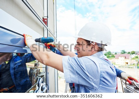 worker builder with hand drill installing glass windows on facade of business building - stock photo
