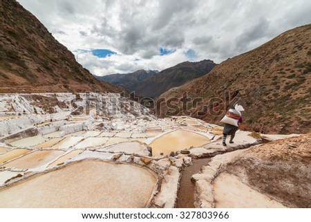 Worker carrying a big sack of salt, on the terraced salt pans in Maras, Urubamba Valley, Peru. Concept of manual work in developing countries. Wide angle image, rear view, unrecognizable person.