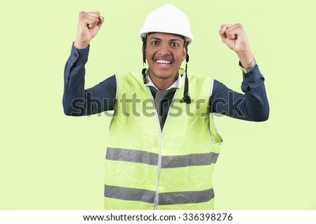 Worker celebrate on green background - stock photo