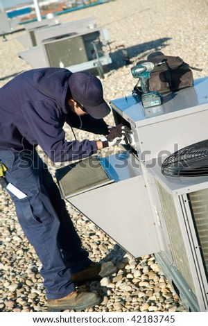 Worker changing a roof top air exchange units filter. - stock photo