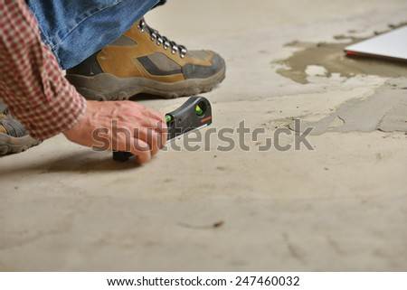 Worker checking the surface using spirit level during the tiled floor installation - stock photo