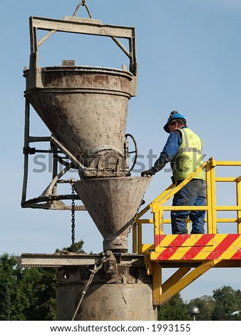 Worker checks cement pouring into the well, close-up - stock photo