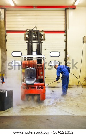 Worker, cleaning a forklift inside out, using a high pressure water jet in a maintenance workshop - stock photo