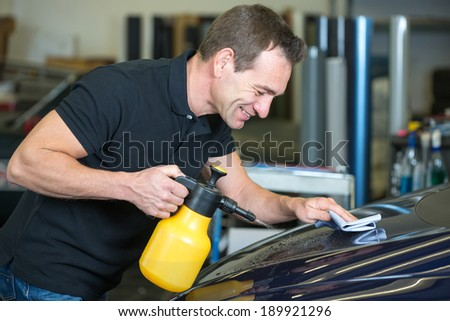 Worker cleaning car with cloth and spray bottle in garage or workshop