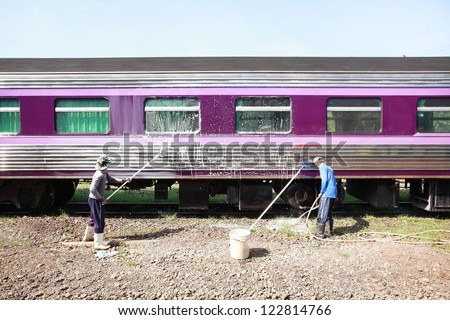 Worker cleaning the train at Trang station Thailand. - stock photo