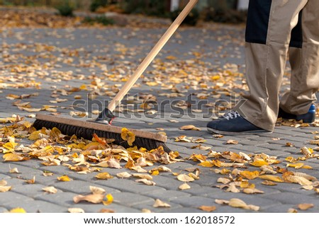 Worker cleaning up the driveway from autumn leaves - stock photo
