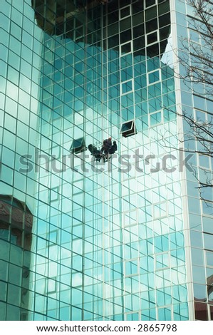 worker climbing at mirror wall of office building - stock photo