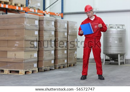 Worker counting stocks in a company warehouse - stock photo