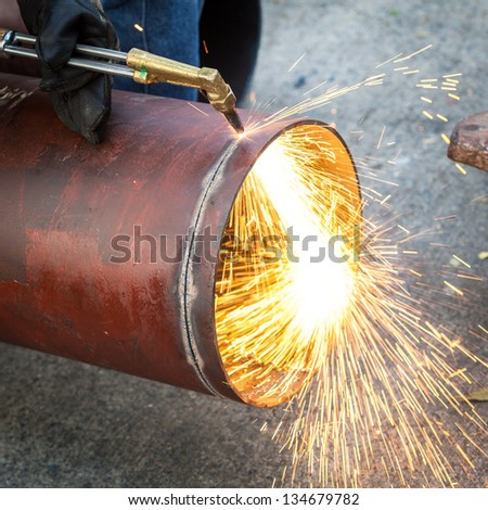 Worker cut big pipe with spark light - stock photo