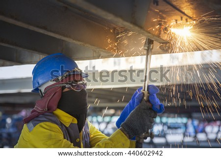 Worker cut the steel base for repair container  with acetylene torch close-up on low ligth - stock photo