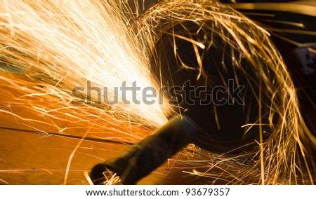 worker cuts a metal pipe by means of the abrasive tool - stock photo