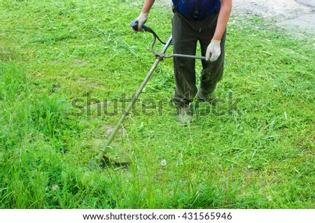 Worker cuts off a grass a lawn-mower - stock photo