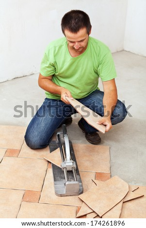 Worker cutting and installing ceramic floor tiles - stock photo