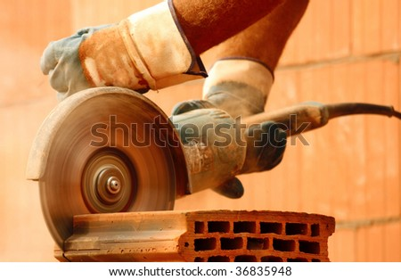 Worker cutting bricks - stock photo