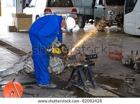 Worker cutting detail with many sharp sparks - stock photo