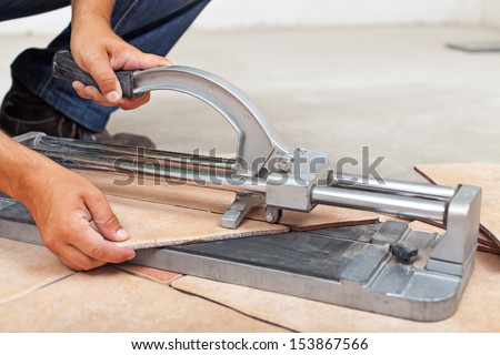 Worker cutting floor tiles with manual cutter - closeup - stock photo
