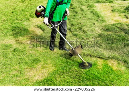 Worker cutting grass using electric lawn mowers. - stock photo
