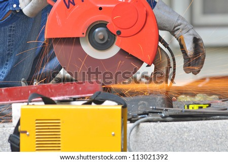 worker cutting metal in construction site