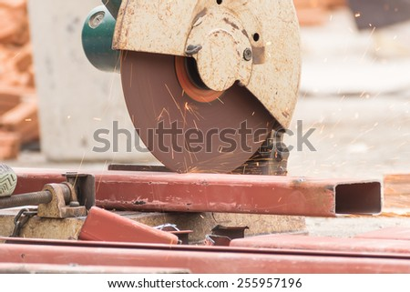 Worker cutting metal with grinder in construction site. Sparks while grinding iron - stock photo