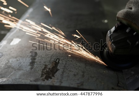 Worker cutting metal with grinder. Sparks while grinding iron Background. Photo is intentionally out of focus, so that we could use for the background. Instagram filter - stock photo