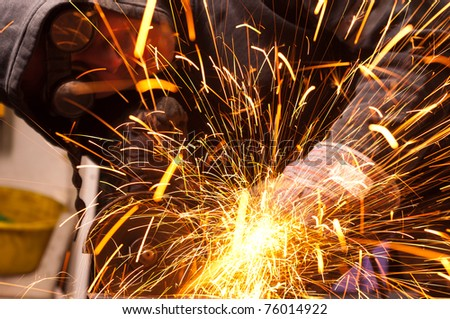 Worker cutting metal with many sharp sparks - stock photo