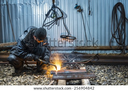 Worker cutting metal with with acetylene torch.