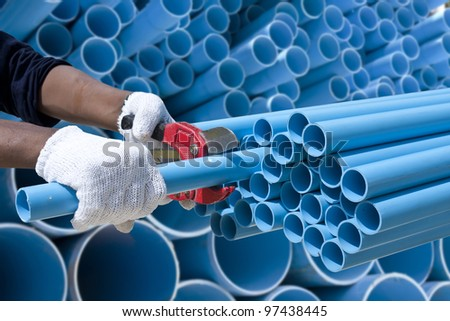 Worker cutting pvc pipe in construction site
