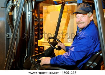 Worker driver of a forklift loader in blue workwear at warehouse - stock photo