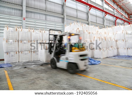worker driving a forklift loader in warehouse with load jumbo bag  - stock photo