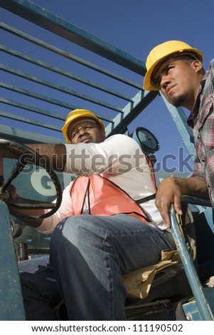 Worker driving a forklift truck at a construction site - stock photo