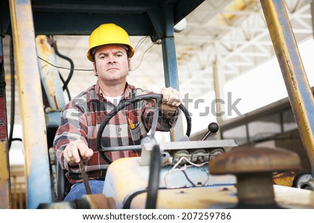 Worker driving heavy construction equipment - bulldozer or backhoe.