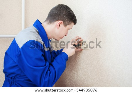 Worker electrician installs an electrical outlet in the apartment