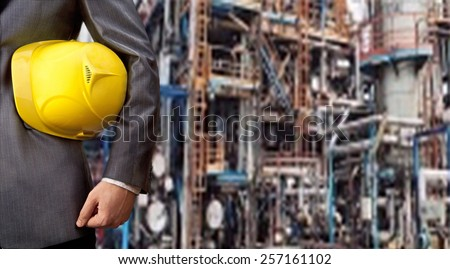 Worker engineer Man work in oil or gas refinery, turning on and off the pipeline valve torso and hand engineer yellow helmet for workers security construction worker No face Unrecognizable person - stock photo