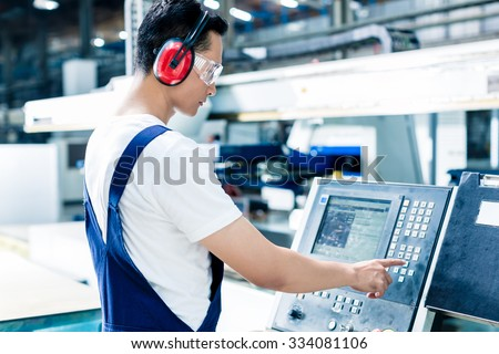 Worker entering data in CNC machine at factory floor to get the production going - stock photo