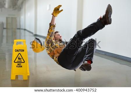 Worker falling on wet floor inside building - stock photo