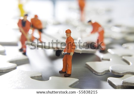 Worker figurines placed with puzzle pieces - stock photo