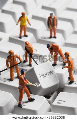Worker figurines posed around the Home key on a computer keyboard. - stock photo